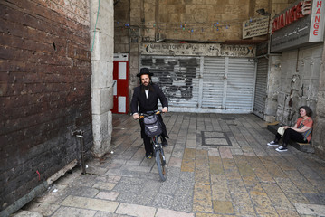 Jewish man rides his bicycle past closed shops during a general strike in solidarity with Palestinian prisoners on hunger strike in Israeli jails, in Jerusalem's Old City