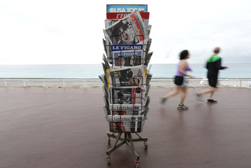 People jog past a news rack which displays copies of French daily newspapers with front pages about France's Presidential election on the Promenade Des Anglais in Nice