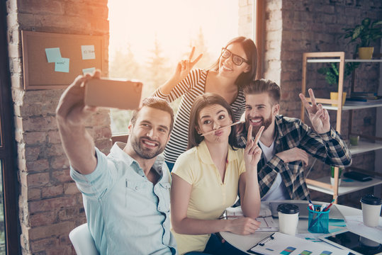 Group of happy smiling people taking a self-portrait in a cafe white having a break