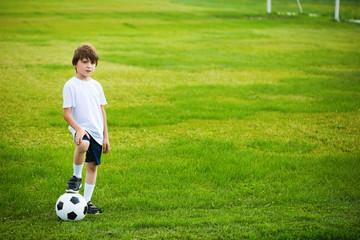 Boy with a soccer ball on a soccer field.
