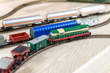 Green model diesel engine pull freight train on light wooden floor, playtime for kids and adults