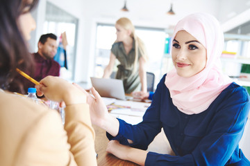 Muslim female coworker carefully listening to advice