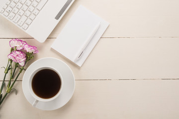 Office table with cup of coffee and flowers