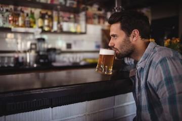 Man drinking beer at counter
