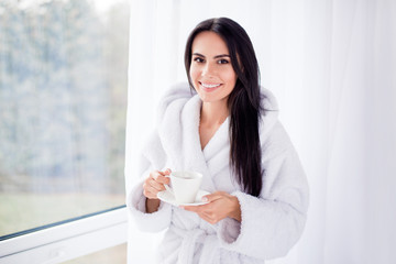 Close up portrait of beautiful brunette girl in bathrobe standing near window. She is smiling and holding a cup of coffee. Nice beginning of day