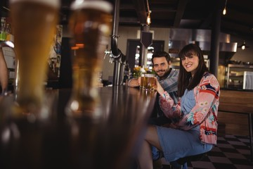 Portrait of happy couple holding glasses of beer at counter