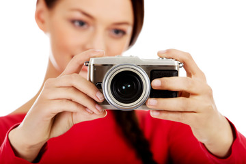 Pretty woman taking a photo using classic slr camera