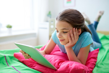 smiling girl with tablet pc lying in bed at home