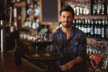 Portrait of bar tender holding a tray with glasses of red wine