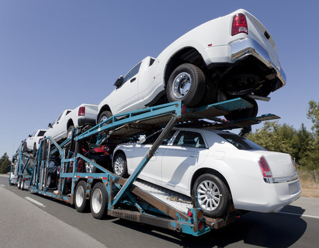 Rear view of trailer of new cars and trucks speeding to market.