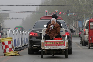 A woman is carried by a motor tricycle on a main road in Xiongxian county