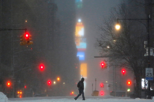 Times Square is seen in the background as a man walks along West 59th street in falling snow in Manhattan, New York