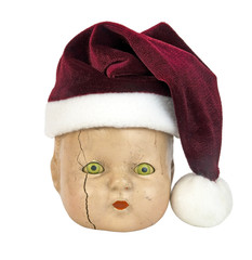 Scary doll head wearing red Santa hat. Creepy. Have a Merry Scary Christmas. Isolated.