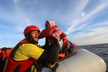 Spanish rescuer Daniel Calvelo, 26, carries a child into a RHIB, during a search and rescue operation by Spanish NGO Proactiva Open Arms, in central Mediterranean Sea, some 22 nautical miles north of the Libyan town of Sabratha