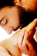 Handsome man kissing woman's foot.