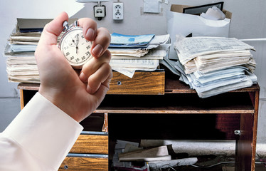 Messy workplace and stopwatch in hand