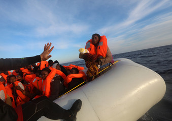 A rescuer tries to find his balance before taking a four-day-old baby girl into a RHIB, during a search and rescue operation by Spanish NGO Proactiva Open Arms, in central Mediterranean Sea
