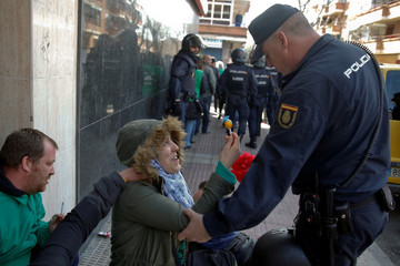An anti-eviction activist offers a lollipop to a Spanish riot policeman in Parla