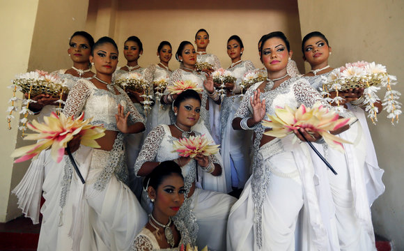 """A group of female traditional dancers pose for photographs during the """"International Women's Day"""" celebrations in Colombo"""