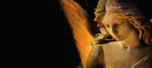 sculpture of an angel with wings against dark background (Religion, faith, Christianity, soul, angel guardian concept)