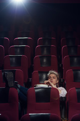 Young blonde woman sitting in movie theater