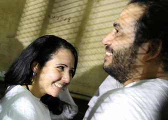 Aya Hijazi and her husband Mohamed Hassanein, founders of Belady, an NGO that promotes a better life for street children, talk inside a holding cell as they face trial on charges of human trafficking at a courthouse in Cairo