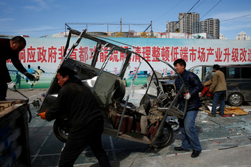 Men load a decommissioned three-wheeled light taxi onto a truck in Beijing