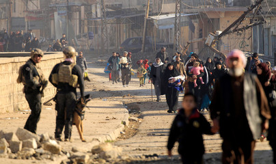 Displaced Iraqis flee their homes in Al Mansour district, as Iraqi forces battle with Islamic State militants, in western Mosul
