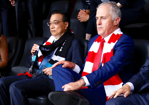 Australia's Prime Minister Malcolm Turnbull sits with Chinese Premier Li Keqiang as they watch an Australian Football League (AFL) game at the Sydney Cricket Ground in Sydney