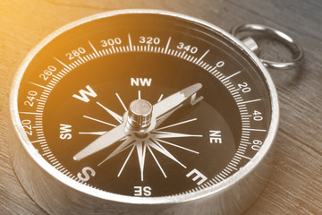 Old vintage retro compass on wooden background