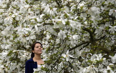 Crump poses as she views Magnolia blossom at Kew Gardens in west London, Britain