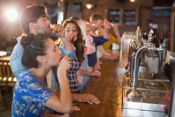 Friends drinking vodka shorts in bar