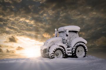 Eingeschneiter Traktor vor einem Sonnenuntergang