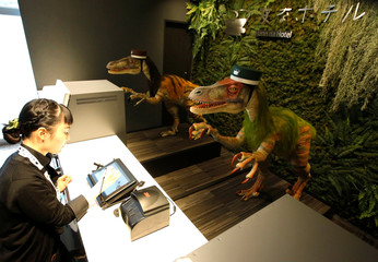 Dinosaur robots acting as receptionist greet a hotel employee demonstrating how to check-in to the hotel during a press preview for the newly-opening Henn na Hotel Maihama Tokyo Bay in Urayasu