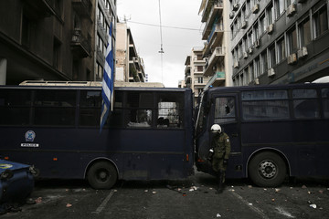 A riot police officer stands next to damaged police buses following clashes of farmers from the island of Crete with riot police outside the Agriculture Ministry in Athens