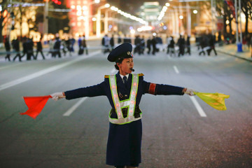 A policewoman controls the traffic as people gather near the main Kim Il Sung square in central Pyongyang
