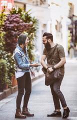 Couple de jeune hipster fouillant un sac dans la rue
