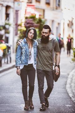 Couple de jeune hipster marchant bras dessus, bras dessous, dans la rue