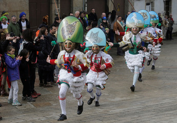 """Carnival revellers dressed as """"Peliqueiros"""" run along a street in the village of Laza"""