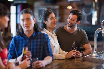 Cheerful friends interacting at bar counter