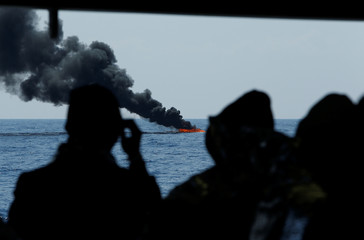 Rescued migrants on board the Malta-based NGO Migrant Offshore Aid Station (MOAS) ship Phoenix watch as their rubber dinghy is burnt in the central Mediterranean north of Sabratha on the Libyan coast