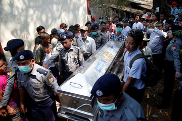 Police carry a victim's body at Pathein General Hospital after a boat with 60 passengers capsized in Pathein river