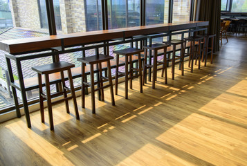 Row of empty bar  chairs and wooden floor