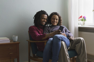 Smiling multi-ethnic couple using smart phone while sitting on armchair at home