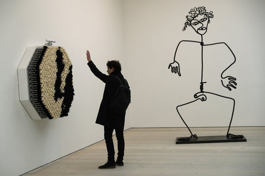 A man looks at 'Pom Pom Mirror' by Daniel Rozin during a press day to promote the upcoming exhibition 'From Selfie to Self-Expression' at the Saatchi Gallery in London