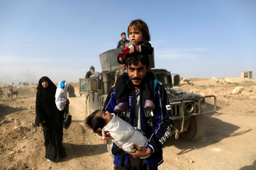 A displaced Iraqi man carries his children as he flees his home, while Iraqi forces battle with Islamic State militants, in western Mosul