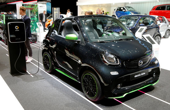 A Smart Fortwo Cabrio Electic Drive car is plugged at a recharging station during the 87th International Motor Show at Palexpo in Geneva
