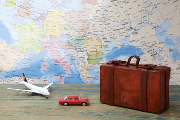 Trip or traveling by airplane concept. Miniature toy airplane and suitcases on map.
