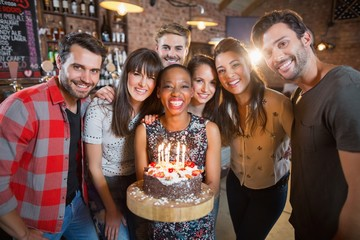 Portrait of happy friends holding birthday cake