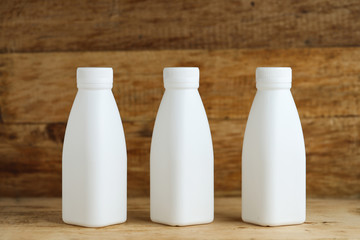 white plastic milk bottles on retro wooden table background